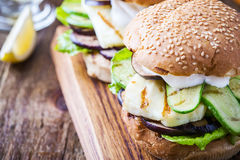 Grilled vegetable and haloumi burger with romaine lettuce. On wooden table, Greek style Stock Image