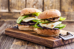 Grilled vegetable and haloumi burger with romaine lettuce. On wooden table, Greek style Stock Photography