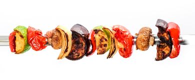 Grilled vegetable kebabs on skewers with cherry tomato, pepper, mushrooms. Squash and onion on white background royalty free stock image