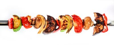Grilled vegetable kebabs on skewers with cherry tomato, pepper, mushrooms. Squash and onion on white background stock photo