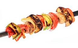 Grilled vegetable kebabs on skewers with cherry tomato, pepper, mushrooms. Squash and onion on white background royalty free stock photography