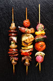 Grilled vegetable and meat skewers  on the black stone background Royalty Free Stock Images