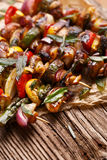 Grilled vegetable and meat skewers on a wooden rustic table Stock Photo