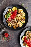Grilled vegetable salad. Salad of barbecued zucchini, eggplant, sweet pepper, onion and mushrooms. On black plate Stock Images
