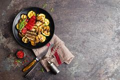 Grilled vegetable salad. Salad of barbecued zucchini, eggplant, sweet pepper, onion and mushrooms on black plate. Stock photo Stock Photos