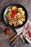 Grilled vegetable salad. Salad of barbecued zucchini, eggplant, sweet pepper, onion and mushrooms on black plate. Stock photo Stock Image