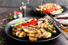 Grilled vegetable salad. Salad of barbecued zucchini, eggplant, sweet pepper, onion and mushrooms on black plate. Stock photo Royalty Free Stock Images