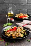 Grilled vegetable salad. Salad of barbecued zucchini, eggplant, sweet pepper, onion and mushrooms on black plate. Stock photo Stock Photography