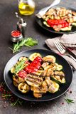 Grilled vegetable salad. Salad of barbecued zucchini, eggplant, sweet pepper, onion and mushrooms on black plate. Stock photo Royalty Free Stock Photo