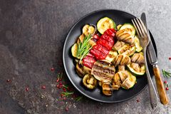 Grilled vegetable salad. Salad of barbecued zucchini, eggplant, sweet pepper, onion and mushrooms on black plate. Stock photo Stock Images