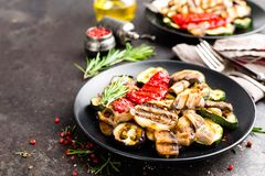 Grilled vegetable salad. Salad of barbecued zucchini, eggplant, sweet pepper, onion and mushrooms. On black plate Royalty Free Stock Photos