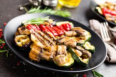 Grilled vegetable salad. Salad of barbecued zucchini, eggplant, sweet pepper, onion and mushrooms. On black plate Stock Photo