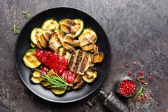 Grilled vegetable salad. Salad of barbecued zucchini, eggplant, sweet pepper, onion and mushrooms. On black plate Royalty Free Stock Photography