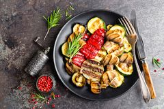 Grilled vegetable salad. Salad of barbecued zucchini, eggplant, sweet pepper, onion and mushrooms. On black plate Stock Photography