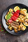 Grilled vegetable salad. Salad of barbecued zucchini, eggplant, sweet pepper, onion and mushrooms. On black plate Royalty Free Stock Image