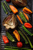 Grilled Vegetables. Assorted grilled vegetables - zucchini, asparagus, artichokes, mini pepper, jalapeno, tomatoes, and carrots - on griddle Stock Photo