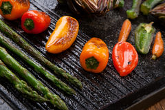 Grilled Vegetables. Assorted grilled vegetables - zucchini, asparagus, artichokes, mini pepper, jalapeno, tomatoes, and carrots - on griddle Stock Image