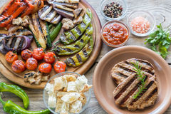 Grilled vegetables with beef steak on the wooden board royalty free stock image