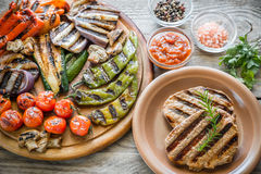Grilled vegetables with beef steaks on the wooden board Royalty Free Stock Photos