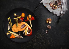 Grilled vegetables in black plate on kitchen table. Colourful grilled vegetables seasoned with mustard in black plate on granitic background royalty free stock images