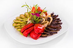 Grilled Vegetables. dish food. Grilled Vegetables Appetizer, eggplant, zucchini, mushrooms, tomatoes and greens.  dish on a white background Stock Photo
