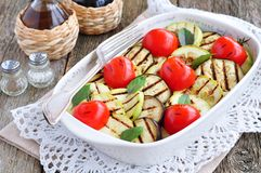 Grilled vegetables eggplant, cherry tomatoe, zucchini with olive oil and basil Royalty Free Stock Image