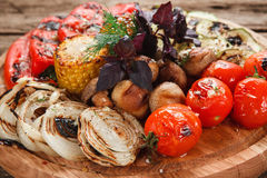 Grilled vegetables mix. Healthy vegetarian food. Delicious grilled vegetables. Tomatoes, red pepper, onion, zucchini, corn and mushrooms decorated with basil Stock Image