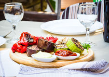Grilled vegetables and mushroom with sauce on a wooden board Royalty Free Stock Image
