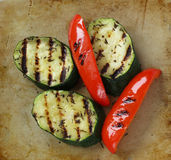 Grilled vegetables on an old rustic stone chopping board Royalty Free Stock Images