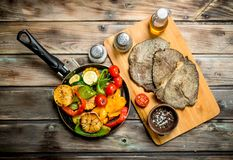 Grilled vegetables in a pan with fried beef steaks stock photos