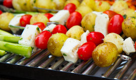 Grilled vegetables. Potatoes, tomatoes and cheese in rotisseries Royalty Free Stock Photography
