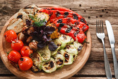 Grilled vegetables served on wood platter top view. Tomatoes, red pepper, onion, zucchini, corn and mushrooms decorated with basil, served with cutlery Stock Photography