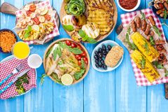 Grilled vegetables, shrimp, fruit on a wooden plate and sausages, juice and salad on a blue background. Summer dinner. Free space. For text. Copy space stock image