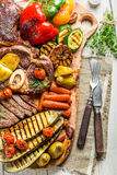 Grilled vegetables and steak with herbs on wooden board Stock Photography