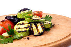 Grilled vegetables on a tray. Zucchini and eggplant with tomatoes after grilling on a wooden cutting board Royalty Free Stock Photos