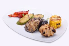 grilled vegetables on a white plate - eggplant, zucchini, champignons, corn and red sweet pepper stock image