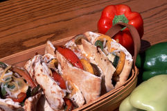 Grilled Veggie Pitas in a Basket. Red, green and white sweet peppers surround basket of grilled vegetable pita sandwiches Stock Photos
