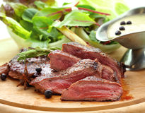 Grilled venison. With fresh vegetables on wood plate Stock Photos