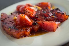 Grilled Garlic Watermelon. Grilled watermelon with fresh roasted garlic and grape tomatoes Stock Images