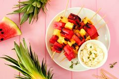 Grilled summer watermelon and pineapple fruit kabobs with feta, above view over pink wood stock image
