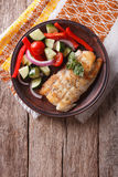 Grilled white fish with vegetables. vertical top view. Grilled white fish with fresh vegetables on a plate. vertical view from above, rustic stock photos