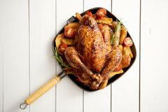 Grilled whole chicken in cast iron black pan with potatoes, tomatos and rosemary stock images