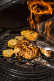 Grilled whole chicken with corn on hot flaming grill. Barbecue. Restaurant Royalty Free Stock Images