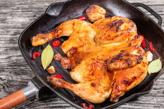 Grilled whole chicken in grill pan with garlic Stock Photography
