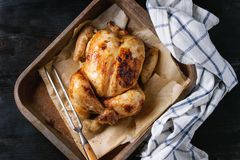 Grilled whole organic chicken. Grilled baked whole organic chicken on backing paper in old oven tray with white kitchen towel and meat fork over black burnt Royalty Free Stock Image