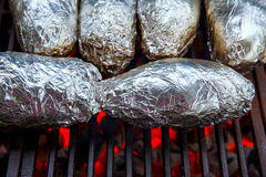 Grilled whole potatoes with foil Royalty Free Stock Photos