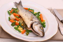 Grilled whole sea bass with vegetables and lemon Royalty Free Stock Photography
