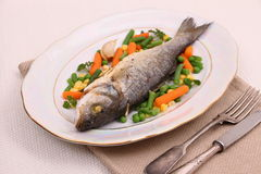 Grilled whole sea bass with vegetables and lemon Royalty Free Stock Images