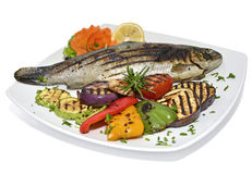 Grilled whole trout with vegetables. On white oval dish isolated on a white background Stock Photo