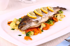 Grilled whole trout, vegetables and lemon Royalty Free Stock Images